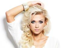 Mooie blonde vrouw met lange krullende haar en stijlmake-up. Royalty-vrije Stock Foto