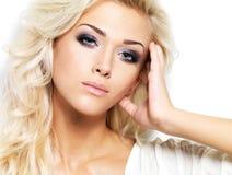 Mooie blonde vrouw met lange krullende haar en stijlmake-up. Royalty-vrije Stock Afbeeldingen