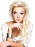 Mooie blonde vrouw met lange krullende haar en stijlmake-up Stock Foto