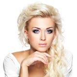 Mooie blonde vrouw met lange krullende haar en stijlmake-up Stock Afbeelding