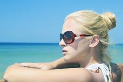 Mooie blonde vrouw op het strand in zonnebril Royalty-vrije Stock Foto's