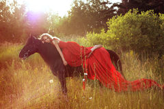 Mooie blonde vrouw in rode kleding bij paard Stock Afbeeldingen