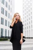 Mooie blonde vrouw in zwarte bedrijfskleren die op telefoon spreken stock fotografie