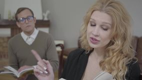 Mooie blonde vrouwenlezing hardop het boek in de voorgrond terwijl bescheiden geklede man die materiaal op bestuderen stock videobeelden