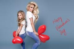 Mooie blondemoeder en dochter die de rode ballons van Valentine houden ` s Stock Foto's