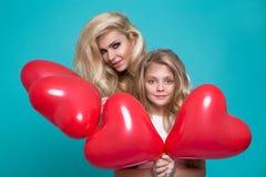 Mooie blondemoeder en dochter die de rode ballons van Valentine houden ` s Royalty-vrije Stock Foto's