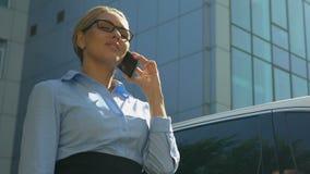 Mooie blondeonderneemster die met partner op cellphone, bodemmening spreken stock video