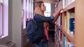 Mooie blondestudent die boek van plank nemen stock footage