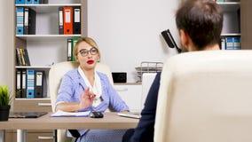 Mooie blondeu vrouw die een kandidaat voor de baan interviewen stock footage