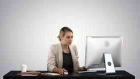 Mooie blondevrouw die aan computer op gradiëntachtergrond werkt stock foto