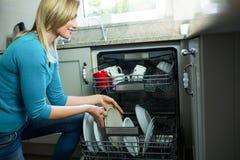 Mooie blondevrouw die de afwasmachine leegmaken stock fotografie