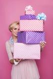 Mooie blondevrouw die door kleurrijke giftdozen kijken Zachte kleuren Kerstmis, verjaardag, Valentine-dag, heden Stock Foto