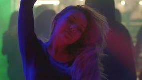 Mooie blondevrouw die, en van atmosfeer genieten bij nachtclubpartij glimlachen dansen stock video