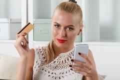 Mooie blondevrouw die gouden krediet houden Stock Afbeelding