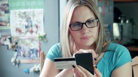 Mooie blondevrouw die online op Internet winkelen stock footage