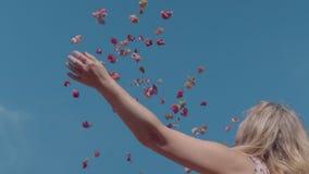Mooie blondevrouw die in roze kleding op roze bloemblaadjes werpen stock footage