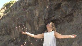 Mooie blondevrouw die in witte kleding op roze bloemblaadjes werpen stock footage