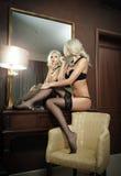 Mooie blondevrouw die in zwarte lingerie spiegel onderzoeken. Jonge mooie vrouw in lingerie het stellen provocatively in hotelruim Royalty-vrije Stock Foto's