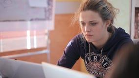 Mooie blondevrouw in een hoodie die aan laptop werken stock videobeelden