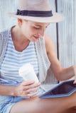 Mooie blondevrouw gebruikend haar tablet en houdend drinkbeker Stock Afbeelding