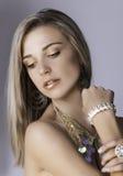 Mooie blondevrouw in goud met juwelen Stock Foto