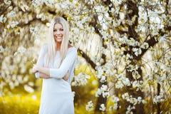 Mooie blondevrouw in het park die zich dichtbij de appelboom bevinden royalty-vrije stock afbeeldingen