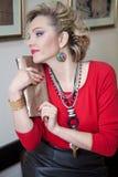 Mooie blondevrouw in het rode sweater stellen in profiel Stock Foto's