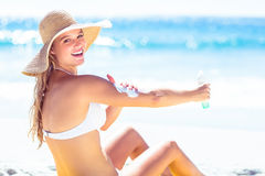 Mooie blondevrouw het uitspreiden zonnebrandolie op haar wapens royalty-vrije stock foto