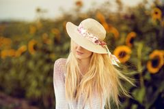Mooie blondevrouw met lang haar en sunhat op een landelijk zonnebloemengebied Stock Afbeelding
