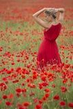 Mooie blondevrouw met rode kleding, in het midden van een papavergebied Stock Afbeeldingen