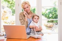 Mooie blondevrouw met zijn zoon die en laptop telefoneren met behulp van Stock Foto