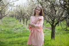 Mooie blondevrouw op de bloemtuin in de lente royalty-vrije stock fotografie
