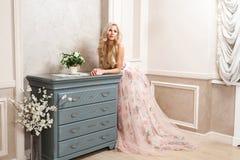 Mooie blondevrouw in pastelkleur bloemen lange gezwollen kleding met make-up en lang krullend kapsel die en dichtbij opmaker leun royalty-vrije stock foto
