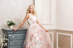 Mooie blondevrouw in pastelkleur bloemen lange gezwollen kleding met make-up en lang krullend kapsel die en dichtbij opmaker leun stock foto's