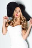 Mooie blondevrouw in zwarte hoed en het witte elegante avondjurk stellen op achtergrond De manier ziet eruit stylish Royalty-vrije Stock Afbeeldingen