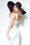 Mooie blondevrouw in zwarte hoed en het witte elegante avondjurk stellen op achtergrond De manier ziet eruit stylish Stock Afbeelding
