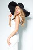 Mooie blondevrouw in zwarte hoed en het witte elegante avondjurk stellen op geïsoleerde achtergrond De manier ziet eruit stylish Royalty-vrije Stock Afbeelding