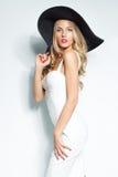 Mooie blondevrouw in zwarte hoed en het witte elegante avondjurk stellen op geïsoleerde achtergrond De manier ziet eruit stylish Royalty-vrije Stock Foto's