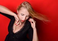 Mooie blondevrouw in zwarte kleding met op een kier borst Royalty-vrije Stock Afbeelding