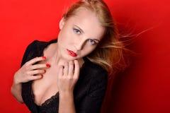 Mooie blondevrouw in zwarte kleding met op een kier borst Royalty-vrije Stock Foto