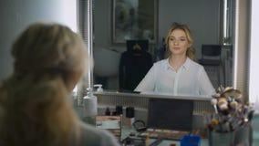 Mooie blondezitting in de schoonheidssalon, heeft zij een uitstekend samenstelling en een kapsel Zij bekijkt zich stock video