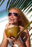 Mooie blondy holdingskokosnoot in tropisch strand Royalty-vrije Stock Afbeelding