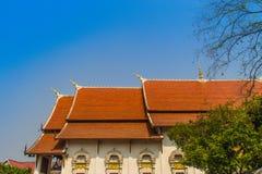 Mooie Boeddhistische kerk, ubosot heiligdomszaal met zijn expansief oranje tegelsdak onder blauwe hemel Oranje en rode daktegels  stock afbeelding