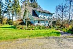 Mooie boerderij met open dek en charmant bloembed Stock Afbeeldingen
