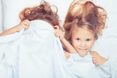 Mooie broer en zuster die in bed thuis liggen Royalty-vrije Stock Afbeeldingen