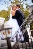 Mooie bruid die bruidegom bekijken en handen op zijn schouder houden Stock Afbeeldingen