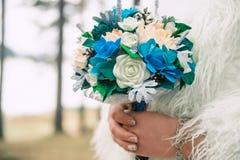 Mooie bruid die een huwelijksboeket van abrikoos en blauwe rozen houden stock fotografie