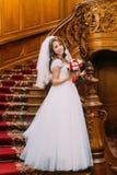 Mooie bruid die in huwelijkskleding een leuk boeket met rode en witte rozen houden die op achtergrond van uitstekende houten stel Stock Foto's