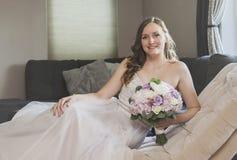 Mooie bruid die op chaise zitkamer liggen Stock Afbeelding