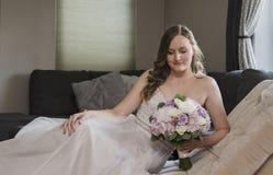Mooie bruid die op chaise zitkamer liggen Stock Afbeeldingen